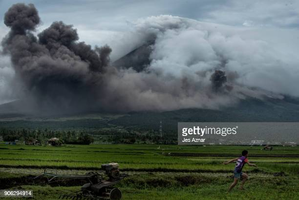 A boy runs as pyroclastic clouds emit from Mayon volcano on January 17 2018 in Camalig Philippines Thousands evacuate as Philippines' Mayon volcano...
