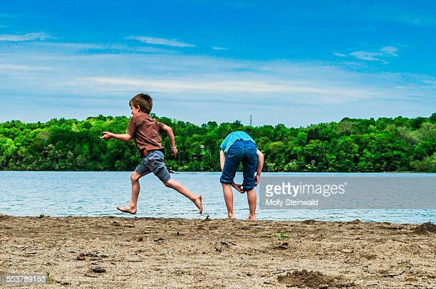 A boy runs by a girl at the waters edge at Hueston Woods State Park OH.