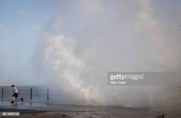 A boy runs from waves whipped up by Hurricane Ophelia as they crash over the seafront in Penzance on October 16 2017 in Cornwall England Hurricane...