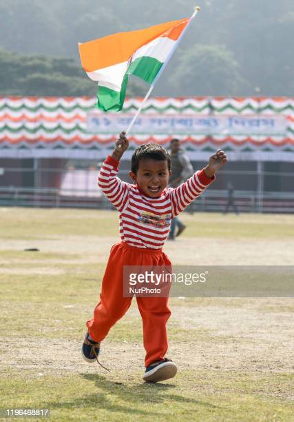 A boy runs holding an Indian Flag during 71st Republic Day celebrations at Veterinary College Playground Khanapara in Guwahati Assam India on 26 Jan...