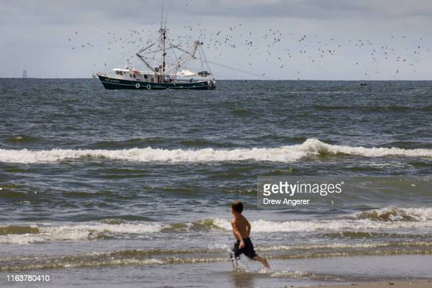 A boy runs into the water as a fishing trawler moves through the Gulf of Mexico off the coast of Grand Isle Louisiana on August 24 2019 According to...