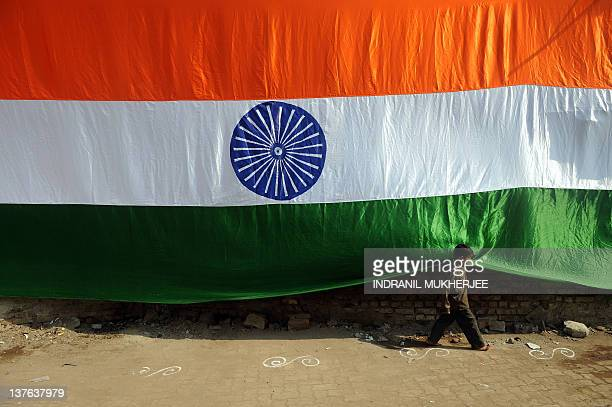 A boy runs past a over 150 feet long hand made Indian national flag hung in one of the narrow bylanes of the Dharavi slum in Mumbai on January 24...