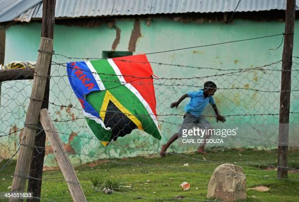 A boy runs past a South African flag near the former home of the late former South African president Nelson Mandela in Qunu on December 9 2013 Qunu...