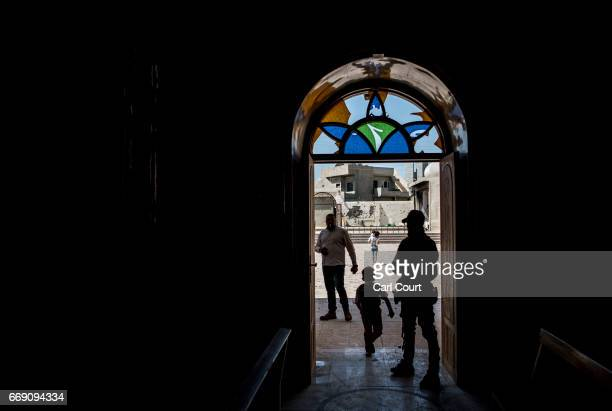 A boy runs past a Syriac Christian militiaman as he guards Saint John's Church during an easter ceremony in the nearly deserted predominantly...