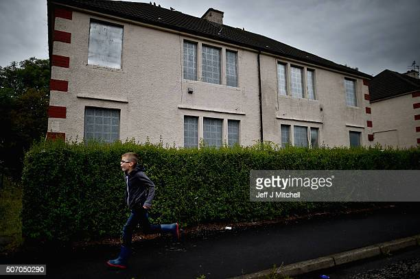 A boy runs past houses that are boarded up in the Ferguslie Park area on July 28 2015 in GlasgowScotland Thousands of households in the UK are...