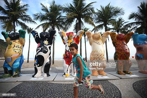 A boy runs past some of the 145 bear sculptures that form the 'United Buddy Bears' exhibition along famed Copacabana beach on May 6 2014 in Rio de...