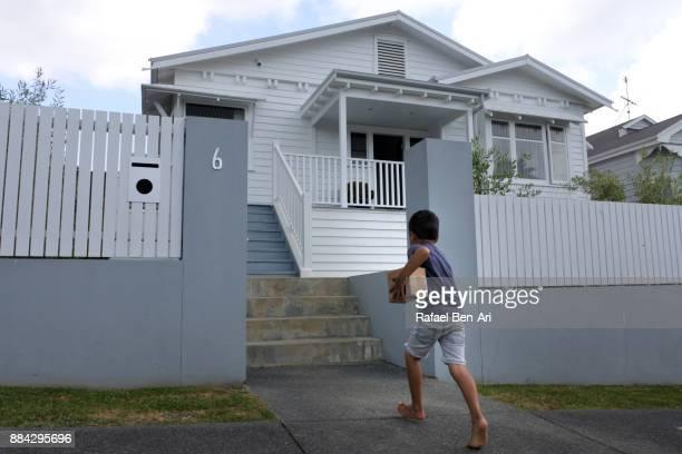 boy runs towards his home with a package in his hand - rafael ben ari stockfoto's en -beelden