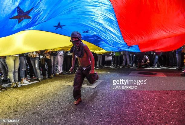 TOPSHOT A boy runs under a Venezuelan flag during a protest of journalists and media workers against the attacks on journalists in Caracas on June 27...