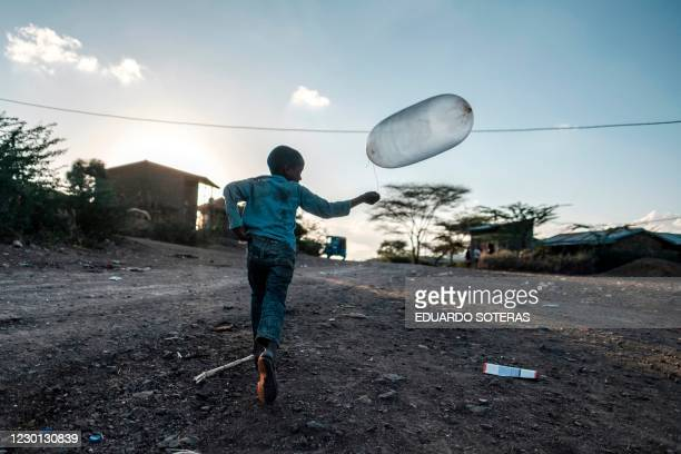 Boy runs with a balloon in the village of Bisober, in Ethiopia's Tigray region on December 9, 2020. - The November 14 killings represent just one...