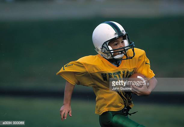 boy runs with football - rush american football stock pictures, royalty-free photos & images
