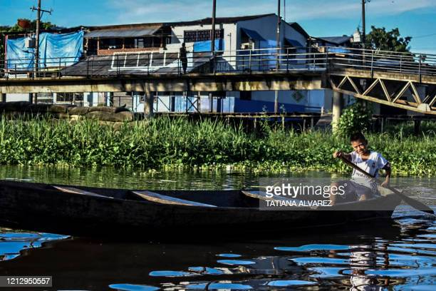 Boy sails at the Amazon river in Leticia, Colombia on May 13 amid the new coronavirus pandemic. - Colombia will increase the presence of military...