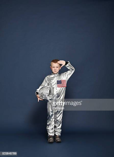 Boy saluting, dressed as an astronaut