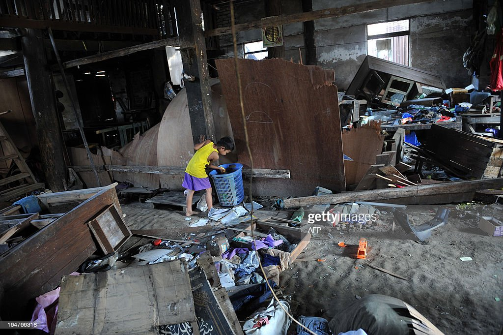 A boy salvages items from his ransacked home after sectarian violence spread through central Myanmar, in Zeegone, Bago division on March 28, 2013. A mosque and Muslim homes were destroyed by hundreds of people in the town of Zeegone about 150 kilometres (90 miles) north of the country's main city Yangon on March 27, the latest outbreak of violence in communal unrest that has left at least 40 people dead. AFP PHOTO/Ye Aung THU