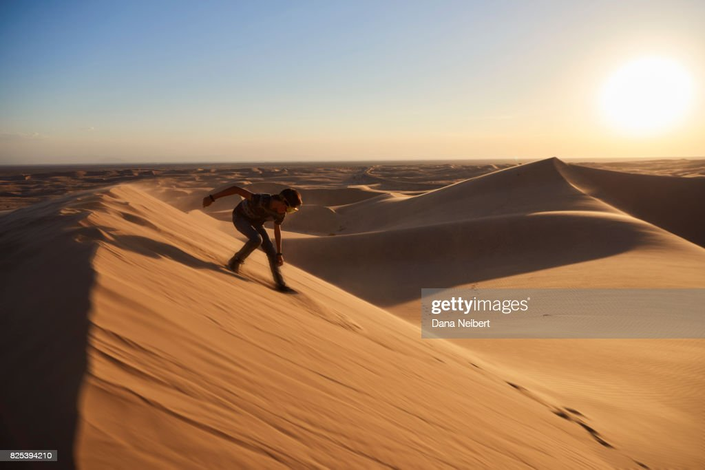 Boy Sand Surfing In The Desert Sand Dunes Stock Photo