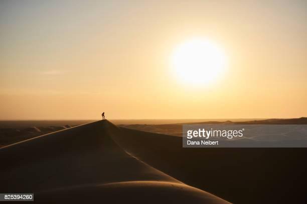 Boy sand surfing in the desert sand dunes