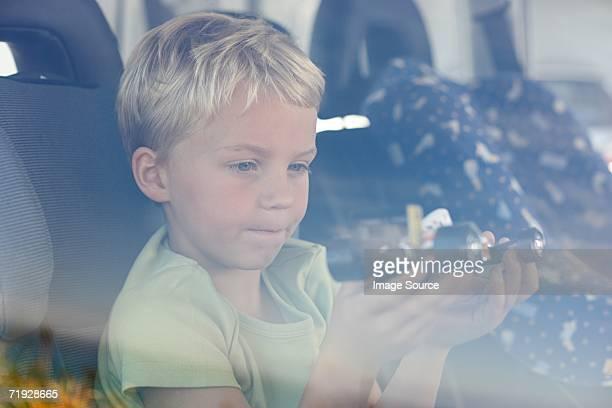 Boy sat in car holding toy car
