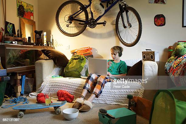 Boy sat in messy bedroom looking at laptop