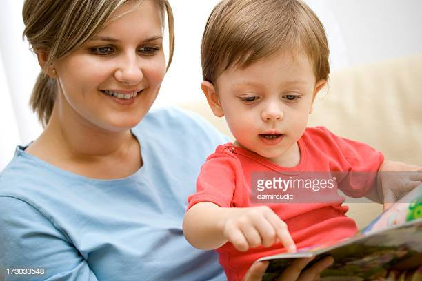 Boy sat on mothers lap pointing at page of book