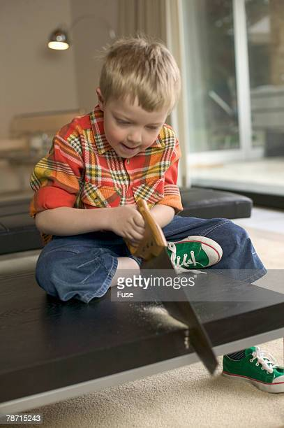 Boy sawing wooden table in living room