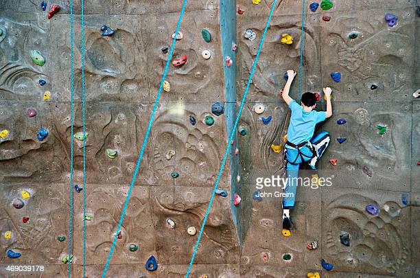 Boy scaling an indoor rock climbing wall