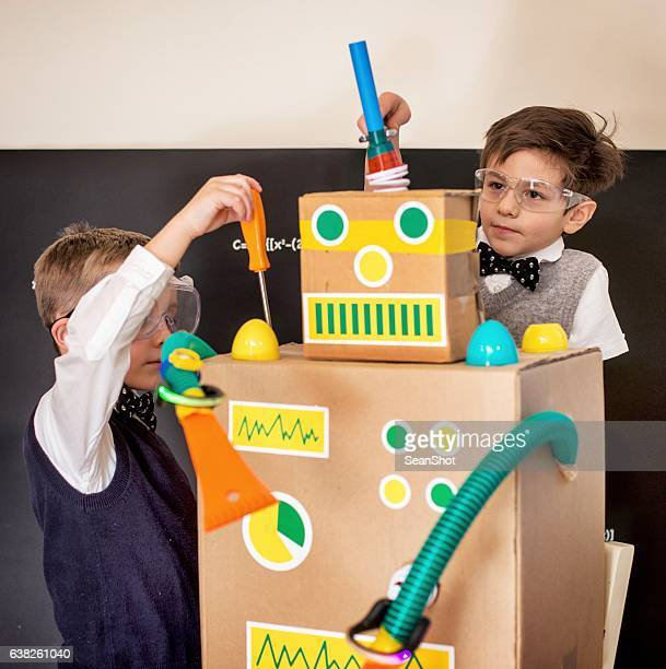 Boy Scientis Fixing Their Toy Robot