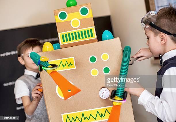 Boy Scientis Fixing Their Toy Robot