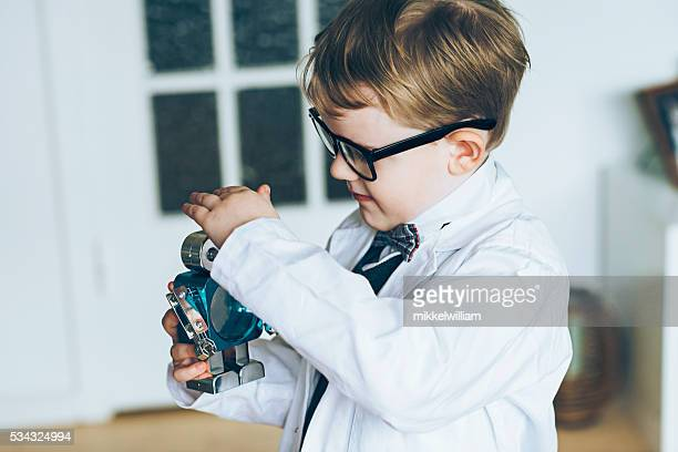 Boy scientist plays with a small toy robot