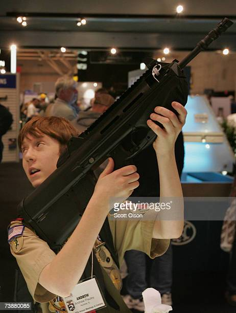 Boy Scout Andrew Pauley looks over a FN rifle during the 136th NRA Annual Meetings and Exhibits April 13 2007 in St Louis Missouri The fourday event...