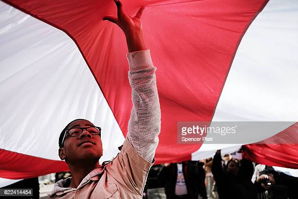 Boy Scout Anthony Tucker holds up an American Flag during the nation's largest Veterans Day Parade in New York City on November 11 2016 in New York...