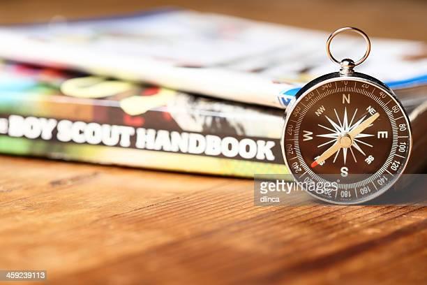 boy scout handbuch mit kompass auf holz tisch - pfadfinder stock-fotos und bilder