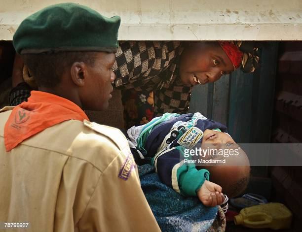 Boy Scout lifts a Kikuyu baby from a truck as it arives at the Nakuru show ground on January 7 2008 in Nakuru Kenya Local volunteers and charities...