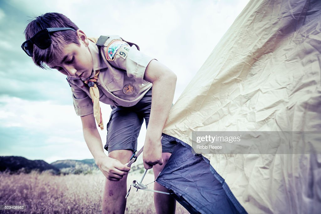 A Boy Scout sets up a camping tent at Boy Scout camp in Colorado. : Stock Photo