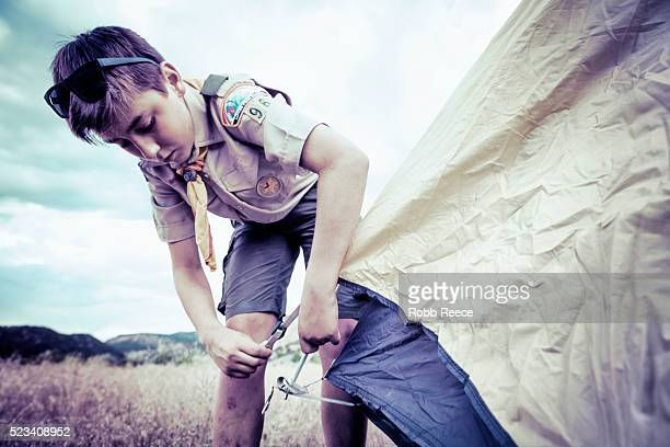 a boy scout sets up a camping tent at boy scout camp in colorado. - robb reece stockfoto's en -beelden