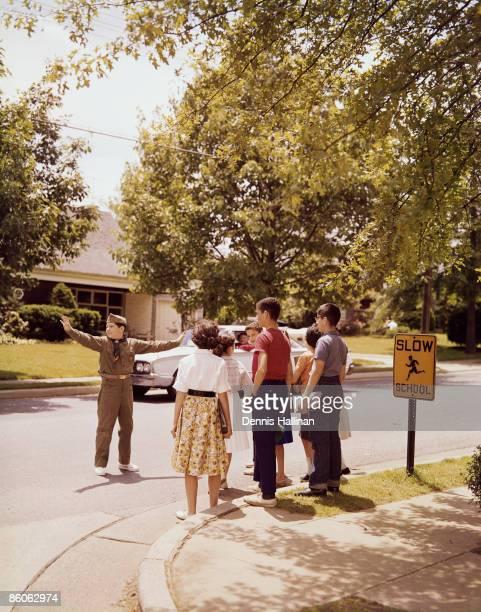 Boy scout stopping traffic for school kids crossing street