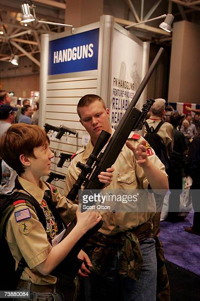Boy Scouts Andrew Pauley and Patrick Wagner look over a FN rifle during the 136th NRA Annual Meetings and Exhibits April 13 2007 in St Louis Missouri...