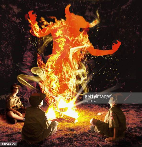 Boy Scouts around campfire, devil emerging from flames (Composite)