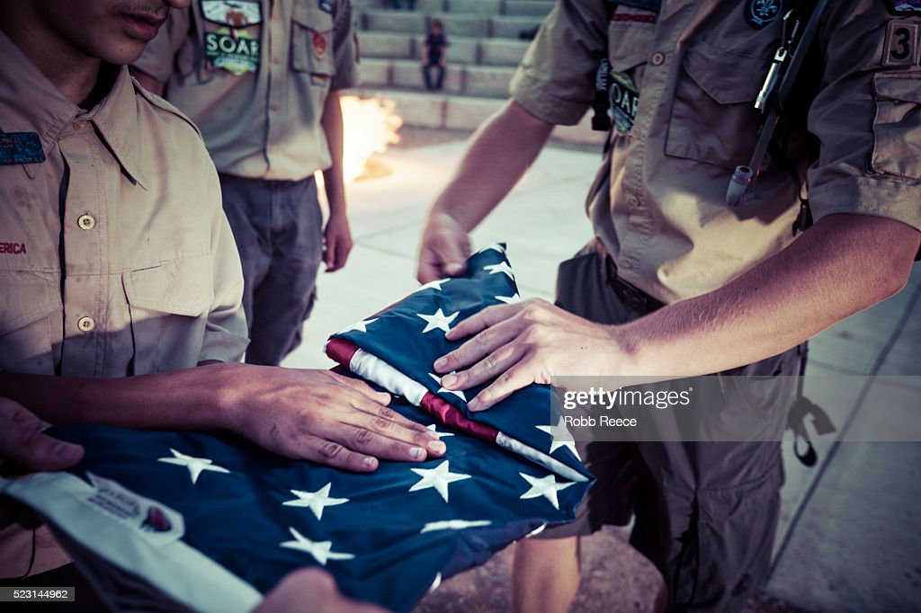 Boy Scouts fold an American flag during a ceremony at their camp in Colorado. : Stock Photo