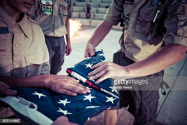 boy scouts fold an american flag during a ceremony at their camp in colorado. - robb reece stock-fotos und bilder