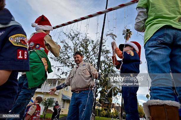 Boy Scouts troop leader Clem Hudson, left, and his son Wesley Hudson right, string Christmas lights on their parade float before the start of the...