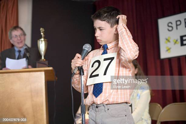 Boy (9-11) scratching head at microphone in spelling bee