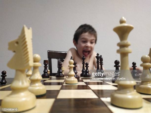 boy screaming while playing chess on table - reality kings stock pictures, royalty-free photos & images