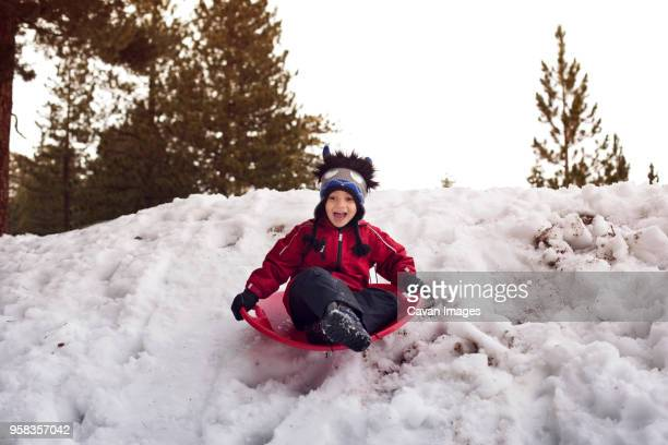 boy screaming while tobogganing on sled at snowfield - snowfield stock pictures, royalty-free photos & images