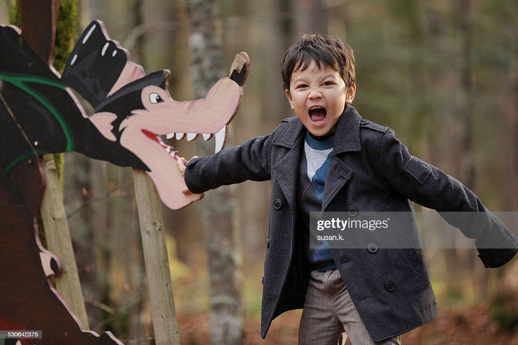 Boy screams pretending to be bitten by big wolf : Stock Photo
