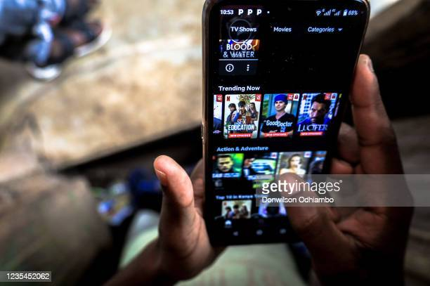 Boy scrolls through his Netflix movie collection using his android smartphone on September 23, 2021 in Nairobi, Kenya. This week, the video-streaming...