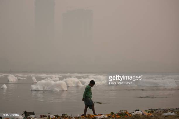 Boy searches for coins on the banks of river Yamuna as people of the city woke up to a hazy morning with monitoring stations across the national...