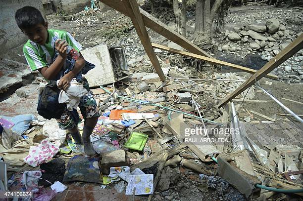 A boy searches through the debris after a landslide earlier this week in Salgar Municipality Antioquia department Colombia on May 20 2015 A massive...