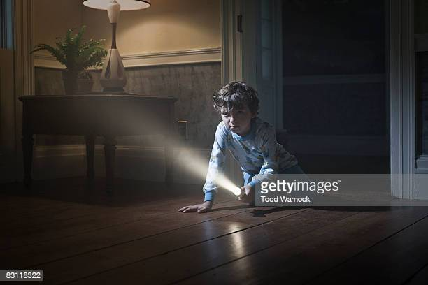 boy searching with flashlight