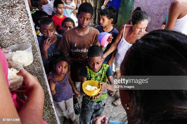 A boy seen carrying out his food Children wait for food in soup kitchens that provides free food on the streets to counteract the food crisis...