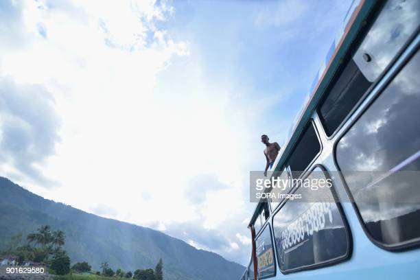 A boy seen on the roof of the ship just before jumping into the lake Toba The Lake Toba in the north of Sumatra as been formed during the occurrence...
