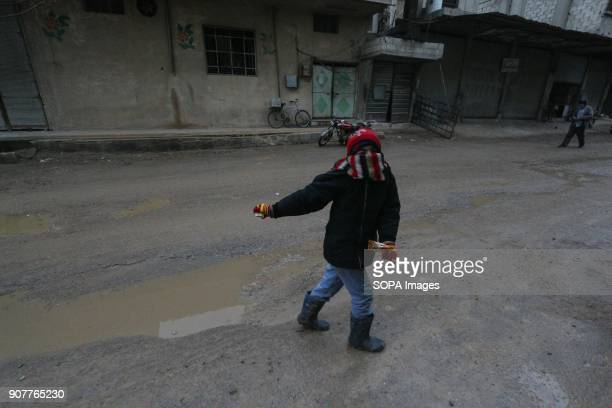 A boy seen playing in the street during the rain in a village outside Damascus Despite the ongoing conflict in Syria life in governmentheld parts of...